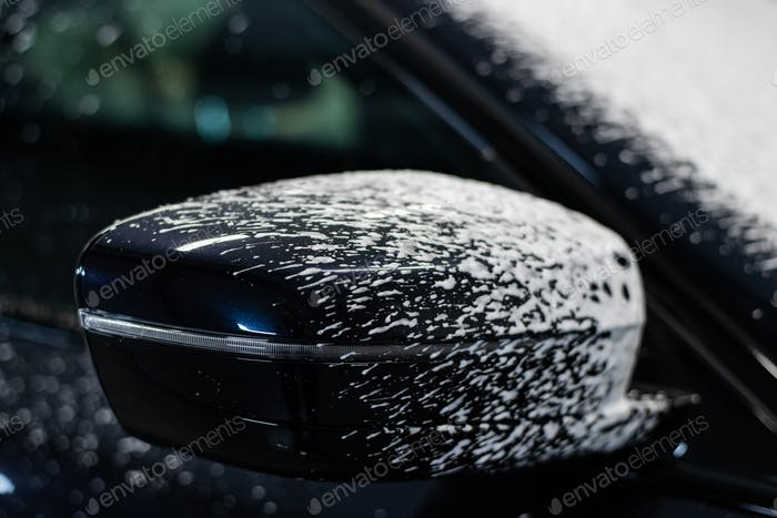 Cleaning car with white snow foam shampoo. Spraying white snow foam on a car. Spraying car shampoo