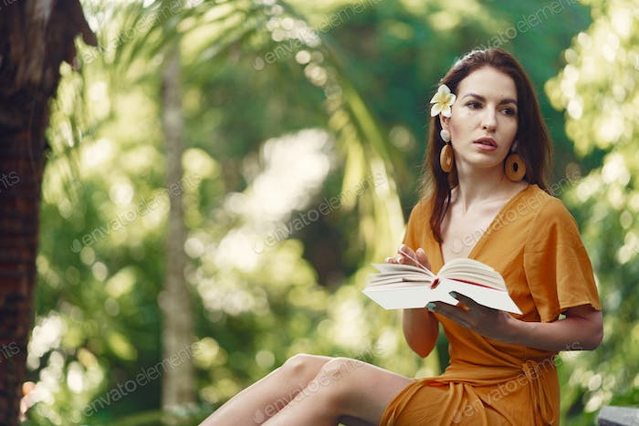 Woman sitting with a book on a jungle background