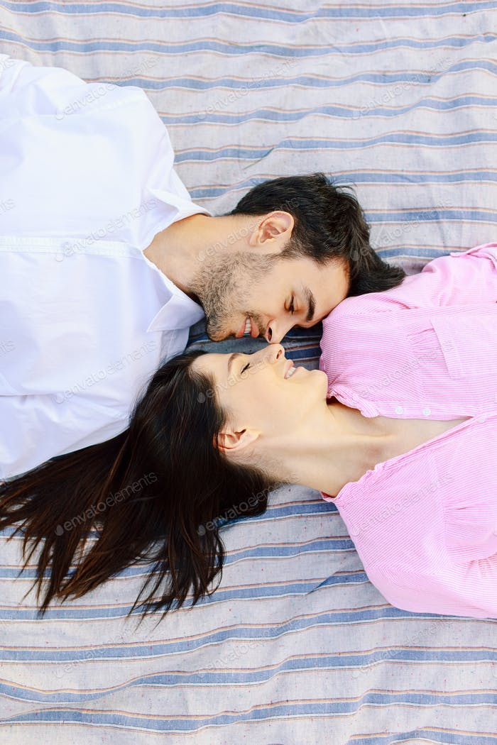 Enjoying closeness top view of beautiful young loving couple lying together.