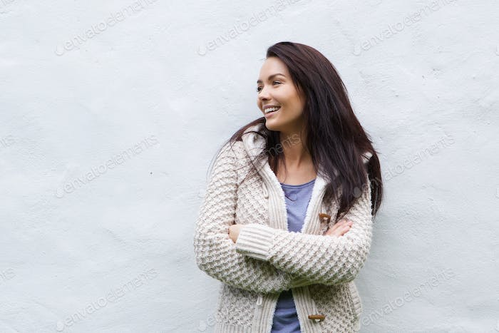 Smiling woman in wool sweater standing against white wall