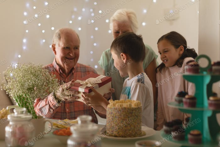 Happy multi-generation family giving present to birthday boy at home with sweet food