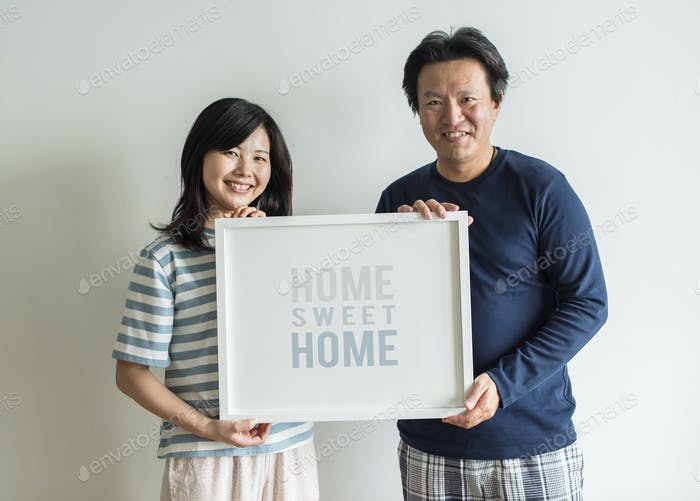 Asian couple holding photo frame together