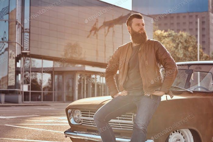 Стильный мужчина опирается на настроенный ретро автомобиль в городской парковке возле небоскреба на ярком закате.