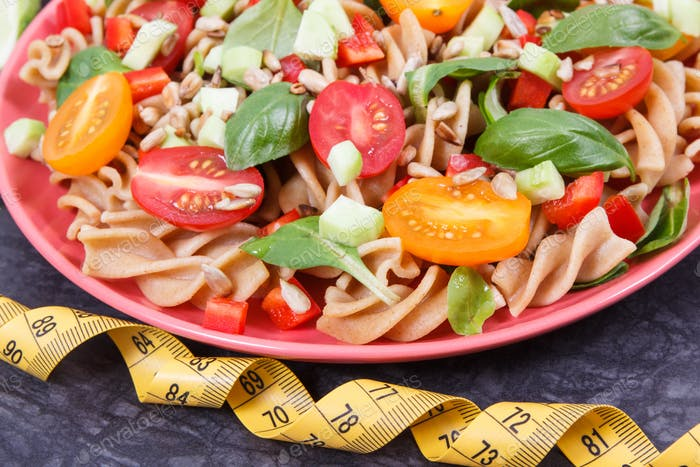 Tape measure and salad with wholegrain pasta and vegetables