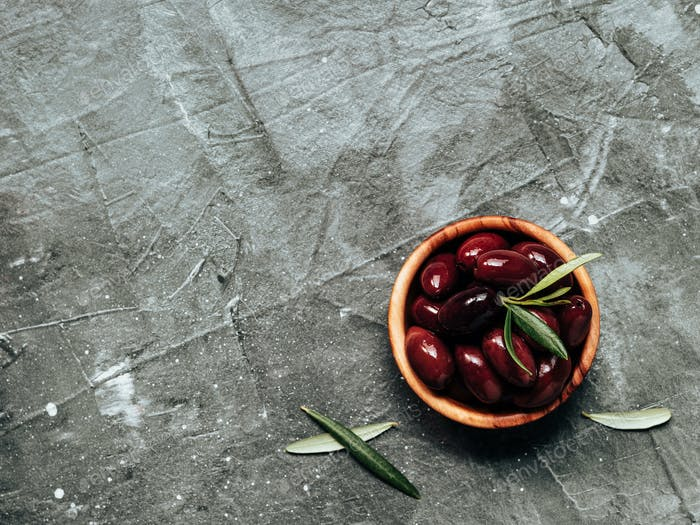 red kalamata olives on gray, copy space