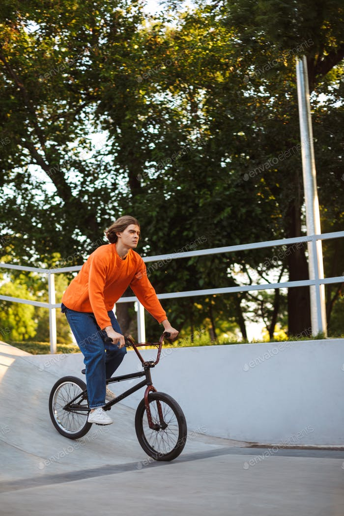 Young guy in orange pullover and jeans riding bicycle at skatepa