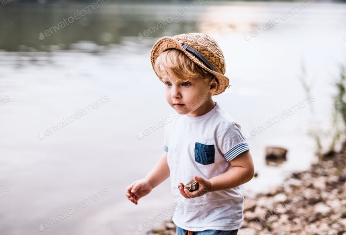 A small toddler boy standing outdoors by a river in summer, playing.