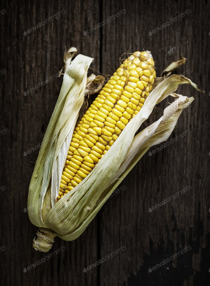 Aerial view of sweencorn cob on wooden background