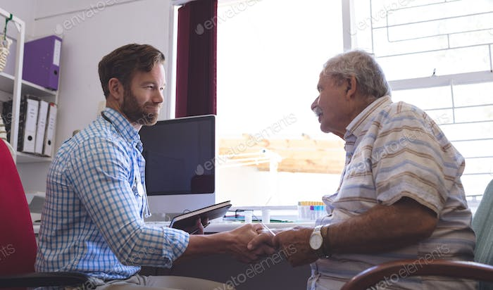 Side view of a Caucasian male doctor and senior man patient interacting with each other in clinic