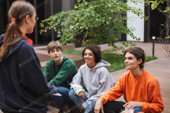 Group of smiling students sitting and happily spending time together in courtyard of university