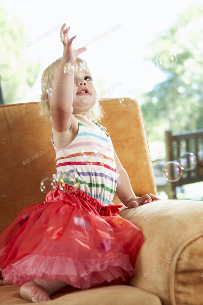 Young Girl Playing With Bubbles On Sofa