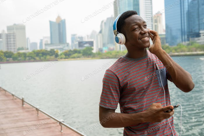 Happy African man in park using mobile phone and listening music with headphones