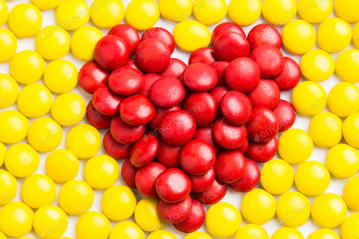 Heart shape red milk chocolate candies with yellow candies backg
