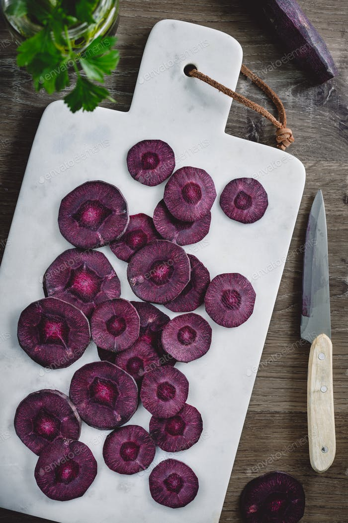 Overhead view on slices of raw purple carrot on a white marble board