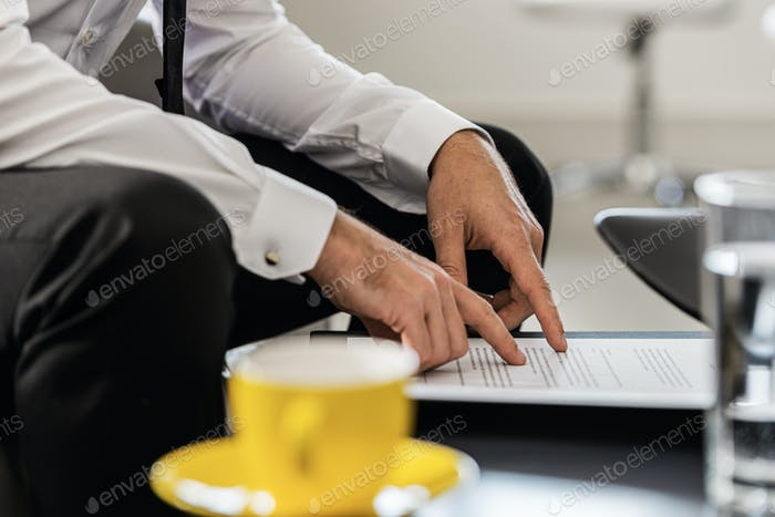 Businessman sitting at an office coffee table proofreading a document