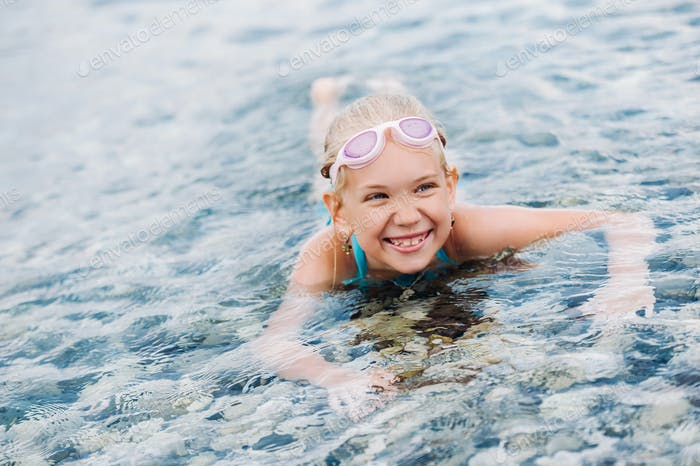 A charming little girl lies in the sea and smiles.A little girl lies in the water laughing.Turkey
