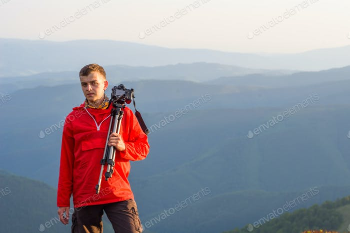 photographer holding a tripod and camera