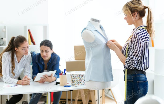 fashion designers working and deciding details of new collection of clothes