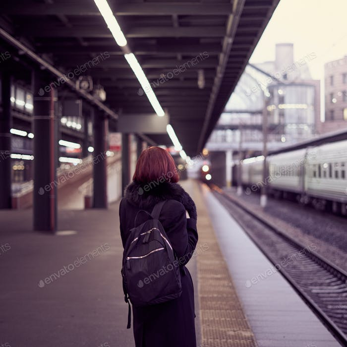 Railway station. Beautiful girl is standing on platform and waiting for train. Woman travels light