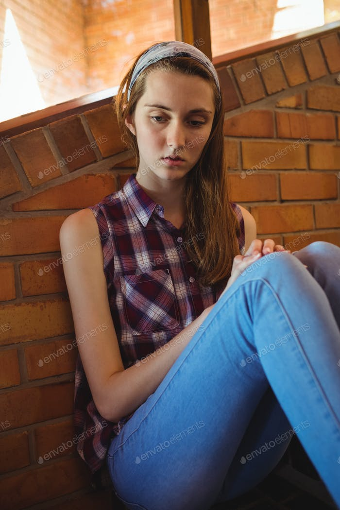 Sad schoolgirl sitting alone on staircase