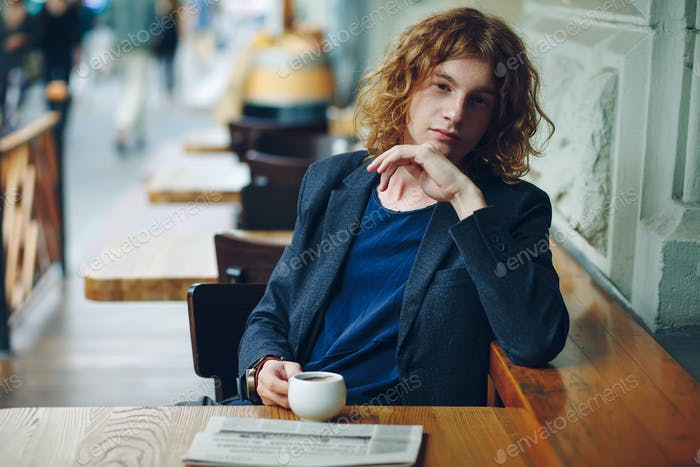 Portrait reddish hipster man with coffe and newspaper