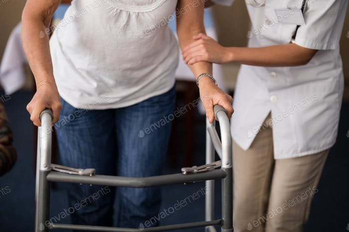 Midsection of female doctor assisting senior woman walking with walker