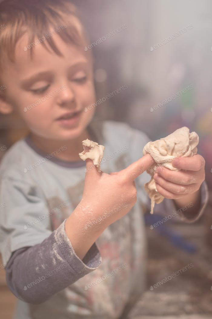 Boy playing with dough in the kitchen