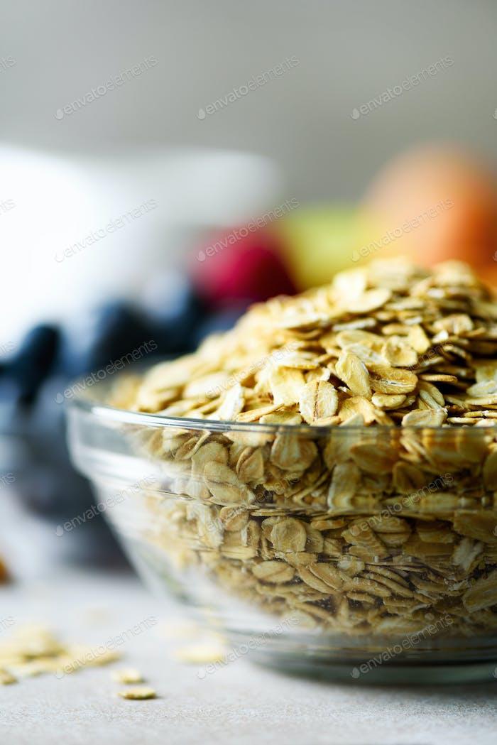 Organic ingredients for healthy breakfast - berries, milk, egg, oatmeal on grey concrete background