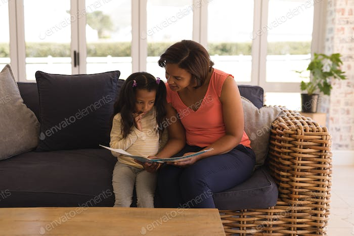 Grandmother and granddaughter reading a story book in living room at home