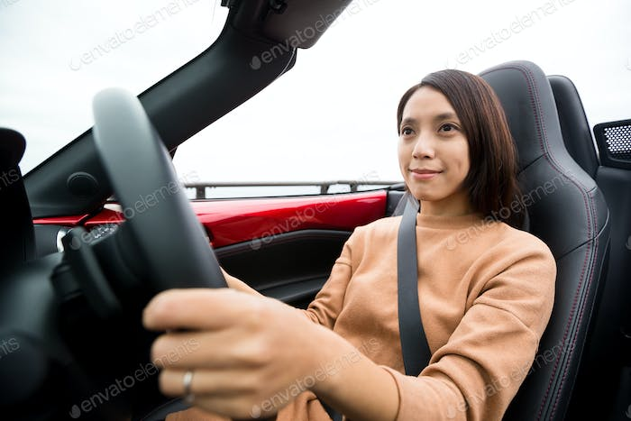 Young woman driving cabriolet