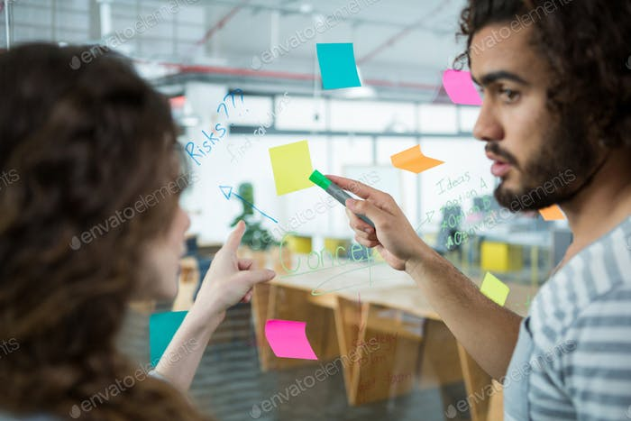 Executives discussing over sticky notes