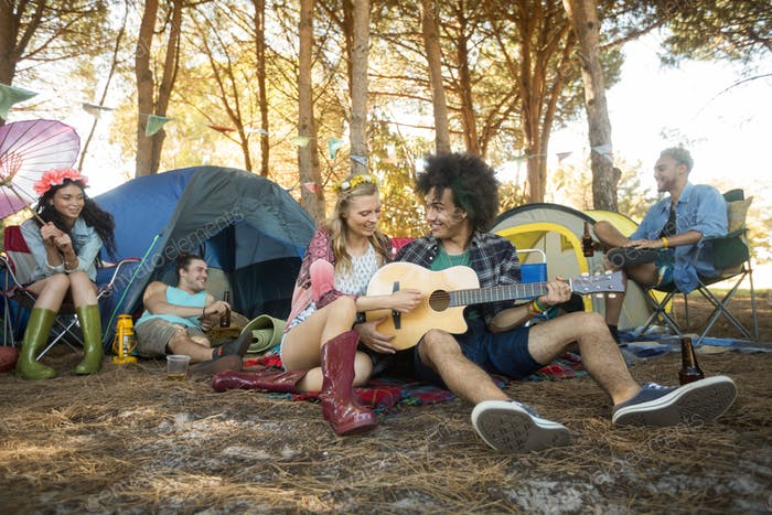 Young woman with male friend playing guitar at campsite