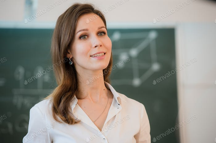 happy teacher standing in front of black board