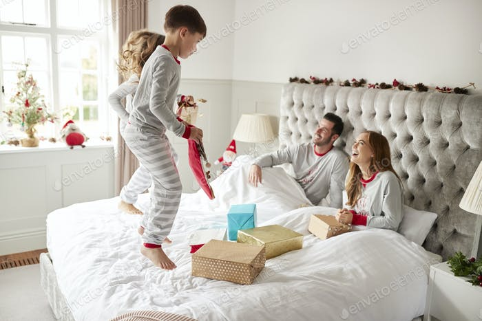 Excited Children Jumping On Parents Bed At Home As Family Open Gifts On Christmas Day
