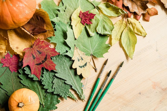 Dry autumn foliage, gourds, halloween faces on leaves and paintbrushes
