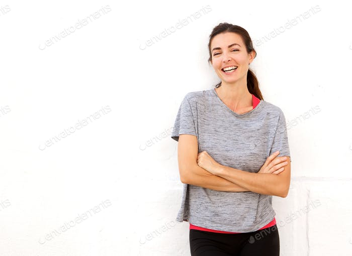 attractive young sports woman smiling with arms crossed against white wall