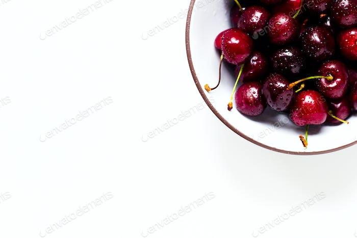 Beeren einer süßen Kirsche mit Wassertropfen in einer Schüssel auf einem weißen Hintergrund