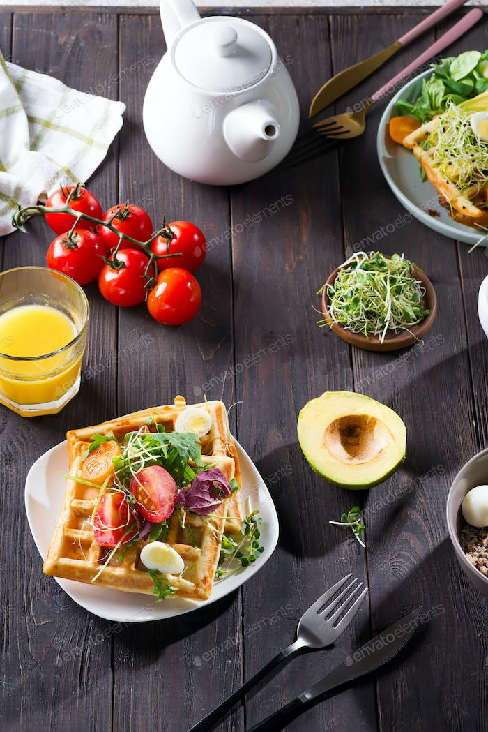 Belgian Waffles with avocado, eggs, micro green and tomatoes with orange juice and tea on wooden
