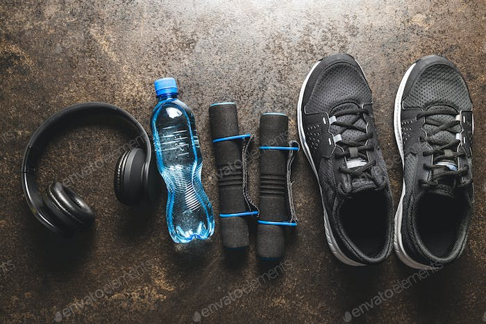 Fitness concept. Black sports shoes, headphones, dumbbell and bottle of water