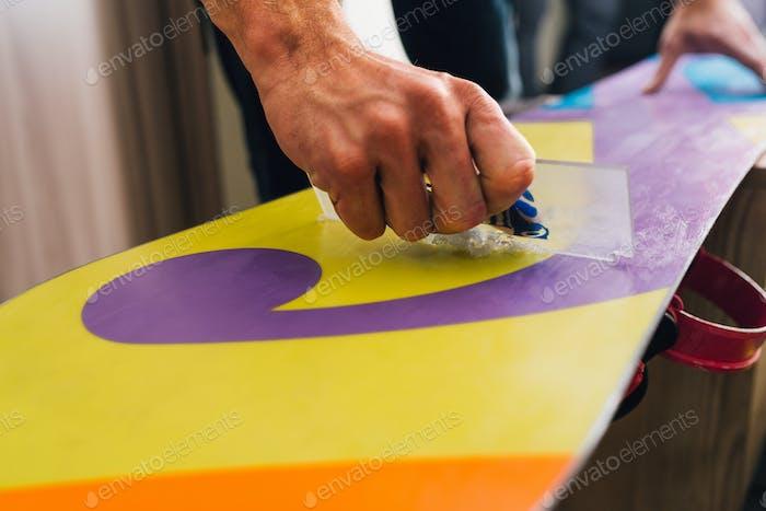 Mann kratzt und scrabing ein Snowboard