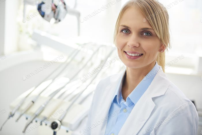 Portrait of smiling dentist in medical uniform in dentist's clinic