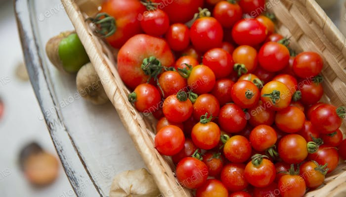 Organic and fresh tomatoes in eco wooden box on chair