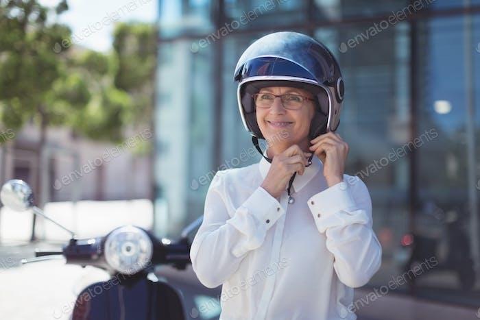 Businesswoman fastening helmet