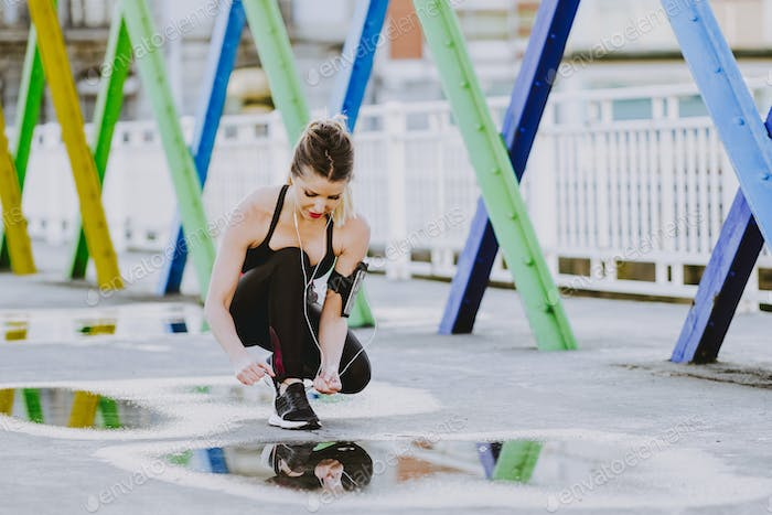 Woman with earphones lacing shoes on street