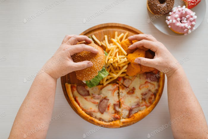 Fat woman hands against high calorie food