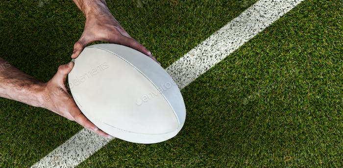 Composite image of man holding rugby ball
