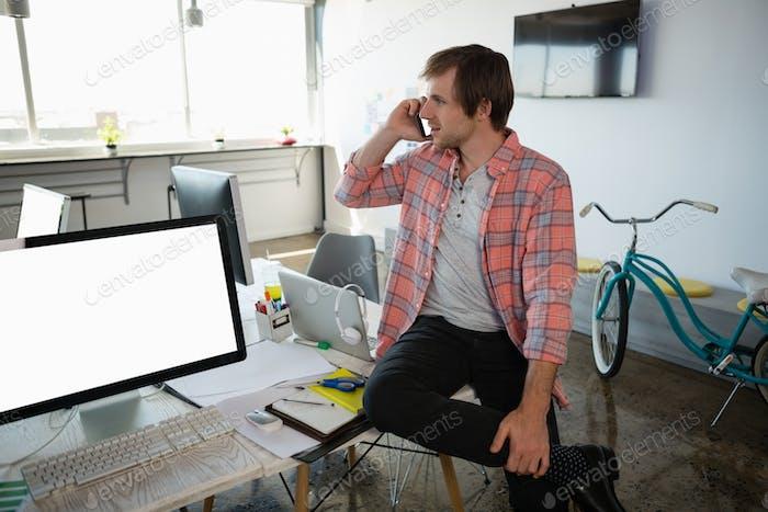 Businessman talking on phone while sitting on desk