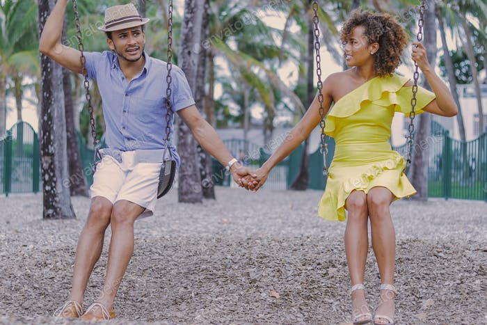 Couple holding hands on swing