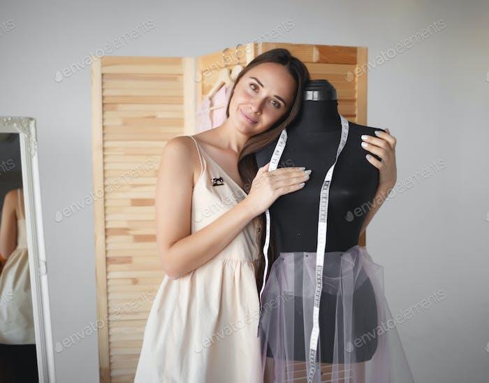 junge schöne Näherin umarmt ein Männchen an ihrem Arbeitsplatz