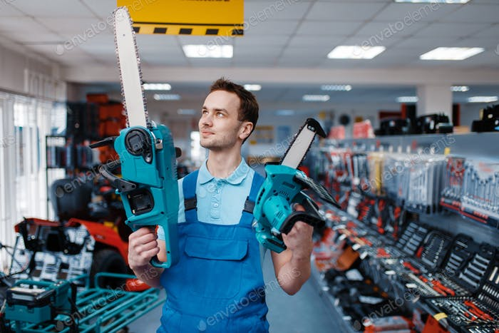 Worker holds big and small chainsaws in tool store